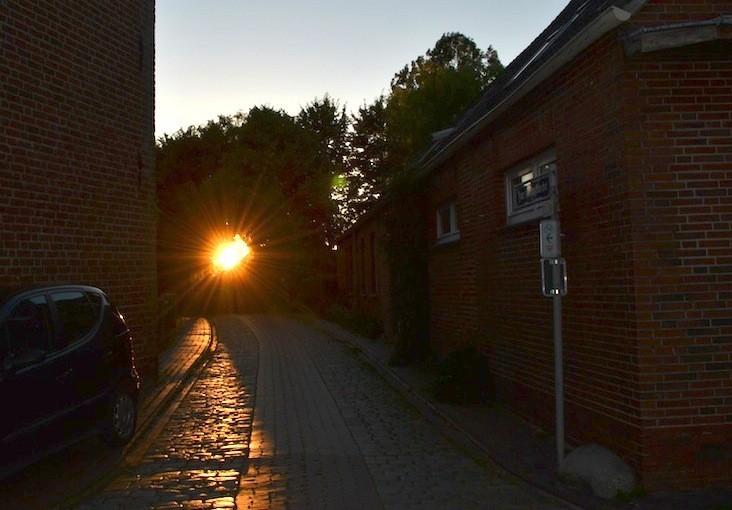 Pilsum an der Kirche Sonnenuntergang durch die Bäume